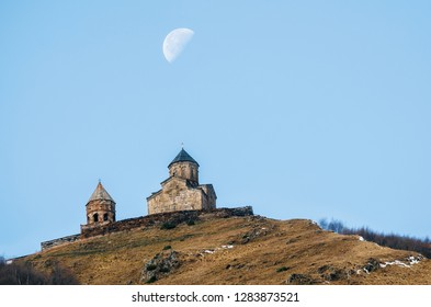 Caucasus mountains, ancient Gergeti Trinity church Tsminda Sameba against blue sky and supermoon, landmark of Georgia