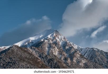 Caucasus mountains. Mount Krasnaya on Arkhyz. Snow peak and mountainside. Trees in the snow.