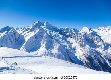 Caucasus Mountains, Panoramic view of the ski slope with the mountains Belalakaya, Sofrudzhu and Sulakhat on the horizon in winter day. Dombai ski resort, Western Caucasus, Karachai-Cherkess, Russia.