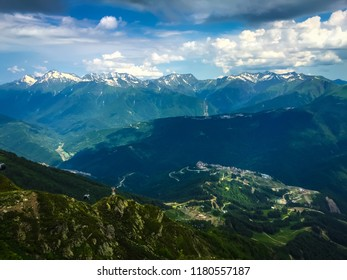 Caucasus Mountains - Rosa Khutor Alpine Resort in Russia, Krasnaya Polyana mountain village. Russian nature with mountains and forest at background. Alpine ski resort in Krasnodar  with Sunny day
