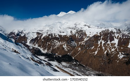 Caucasus mountains winter view with Mount Elbrus on the back and Baksan Valley on the front.