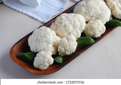 Cauliflower and basil leaves on the table