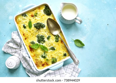Cauliflower broccoli gratin in a baking dish on a light blue slate,stone or concrete background.Top view with copy space.