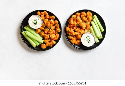 Cauliflower buffalo wings with celery and sauce on plate over white stone background with free text space. Healthy eating, plant based food concept. Top view, flat lay