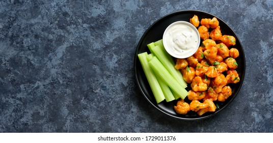 Cauliflower buffalo wings with celery and sauce on plate over blue stone background with free text space. Healthy eating, plant based food concept. Top view, flat lay