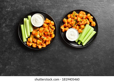 Cauliflower buffalo wings with celery and sauce on plate over black stone background with free text space. Healthy eating, plant based food concept. Top view, flat lay