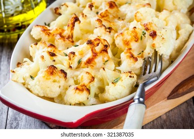 Cauliflower and cheese gratin in the baking dish on wooden table closeup