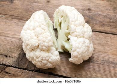 Cauliflower cut in half (like a brain) over wooden background