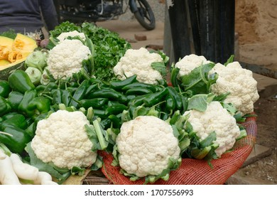 Cauliflower and green chili peppers displayed at an outdoor market in