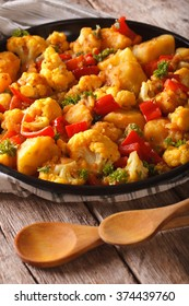 Cauliflower with potatoes in curry sauce on a plate close-up. vertical, rustic