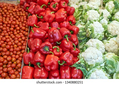 Cauliflower, red peppers and tomatoes for sale at a market
