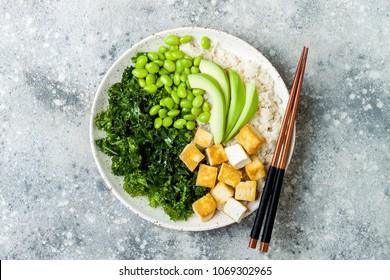 Cauliflower rice Buddha bowl with massaged kale, tofu, avocado and edamame beans. Vegan poke bowl