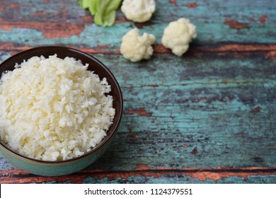 Cauliflower rice on green wooden background, selective focus