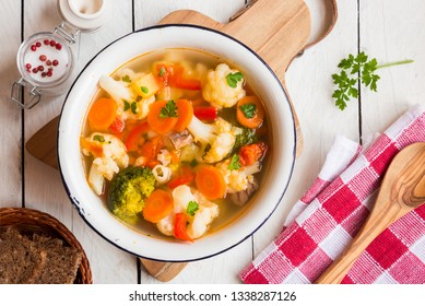 Cauliflower soup with potatoes, carrots and other vegetables on white background