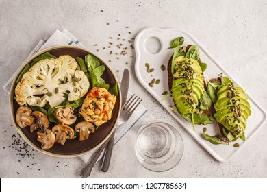 Cauliflower steak with grilled champignons and hummus and avocado toast, top view. Plant based diet concept.