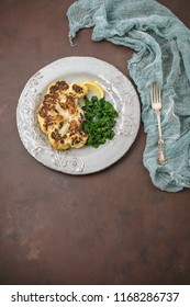 Cauliflower Steak on a Plate with Sauteed Kale and a Lemon Wedge; Brown Background