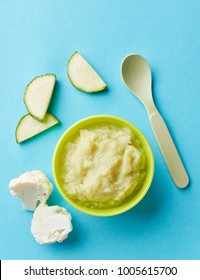 Cauliflower and zucchini baby puree in bowl with baby spoon on blue background, top view
