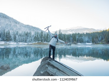Caumasee, Flims / Switzerland -  November 15, 2017: Portrait of a photographer in the top of a rock with Trees and Snow as a Background