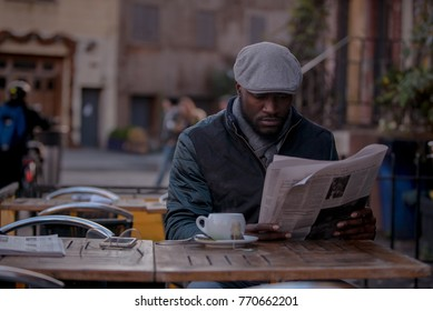 Causal man reading a newspaper at an outdoor coffee shop