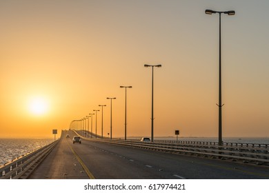 CAUSEWAY, BAHRAIN - 21 SEPTEMBER, 2016: Morning commuter traffic makes its way towards the border as the sun rises at dawn on the King Fahd Causeway highway bridge between Bahrain and Saudi Arabia.
