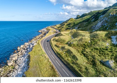 Causeway Coastal Route with cars, a.k.a. Antrim Coastal Road on eastern coast of Northern Ireland, UK.