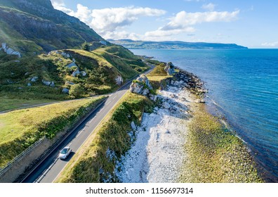 Causeway Costal Route with a car, a.k.a. Antrim Coastal Road on eastern coast of Northern Ireland, UK. Aerial view