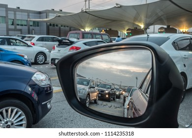 CAUSEWAY ISLAND, BAHRAIN - 25 FEBRUARY, 2017: Reflected in a car wing mirror, traffic bound for Saudi Arabia waits in line at dawn on a congested morning at Bahrain passport control.