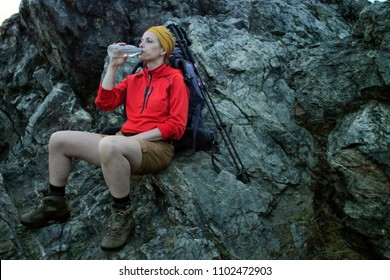 causian female hiker sitting on a rock next to her backpack drinking water out of a bottle