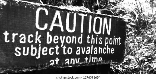 caution avalanche warning sign on trail