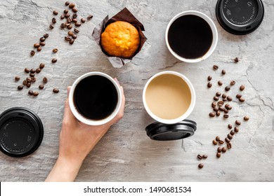 Caution: contents hot. Paper cups with coffee in hands to take away, beans, muffin on gray background top view