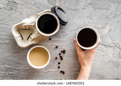 Caution contents hot text. Coffee to take away in paper cups with lids and beans on gray table background top view