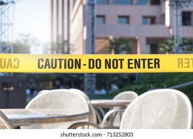 Caution, do not enter line tape and ribbon in city, outdoor terrace, restaurant or building. Construction or crime scene with a warning text. Forbidden, prohibited or restricted area.