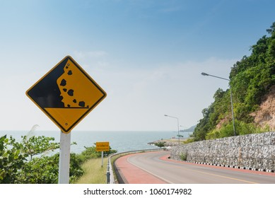 Caution falling rocks sign yellow traffic sign on the road at Thailand.