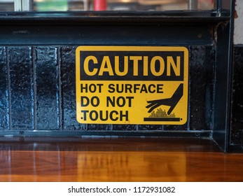 Caution hot surface, do not touch sign at a grill at a restaurant