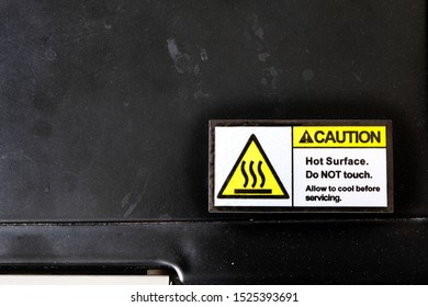 A caution label sticker applied on a metal oven surface, warning users to avoid touching the hot surface. Manufacturers attached such labels as a legal precaution to limit civil & product liability.