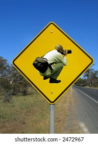 Caution photographers ahead. Funny road sign against the blue sky.