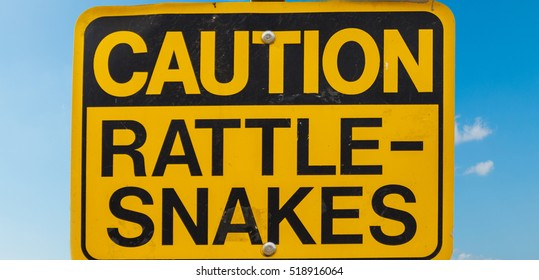 CAUTION RATTLE SNAKES signs under a blue sky