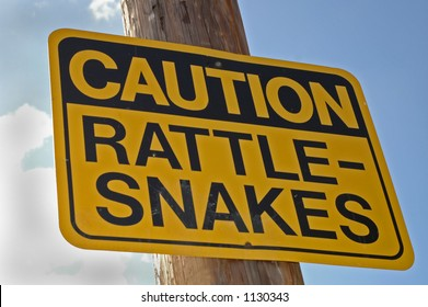"""Caution Rattle-Snake"" sign hanging on post"