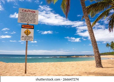 Caution sign about rip currents at beautiful tropical Hawaiian Beach
