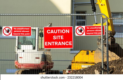 Caution sign at entrance to construction site.Red plaque hanging on the fence in the middle between the two arrays speaking about the ban on entry to the site.