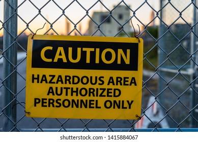 Caution sign for hazardous area on metal fence