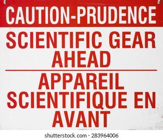 Caution sign. Scientific gear ahead.
