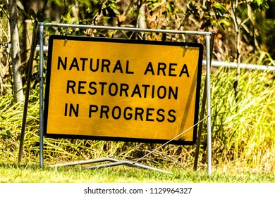 "A caution sign that reads ""Natural Area Restoration In Progress"""