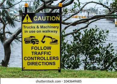 """A caution sign that reads """"Trucks & Machinery In Use On Walkway, Follow Traffic Controllers Directions"""" and displays symbols for a truck and an excavator."""