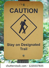 A caution sign warning hikers to stay on designated trails. taken in Nanaimo, Canda, but suitable for any use involving mountains, forests, outdoors, parks, or recreational areas.