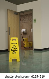 A Caution Sign Warns People Of A Wet Floor In Front Of The Womenu0027s Restroom