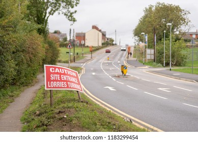 Caution site entrance lorries turning warning road sign on British road daylight view