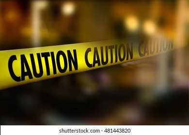 Caution tape and blurred law enforcement and forensic background