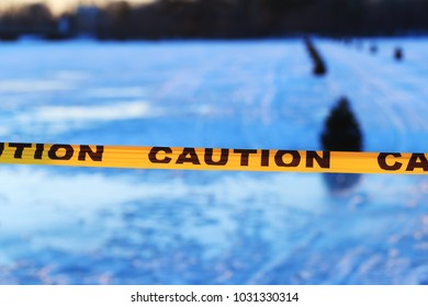 Caution or warning sign of drowning, frozen lake formed by a dam in the winter or at the beginning of the spring. Dangerous frozen lake. Close-up of caution sign of thin ice on the public frozen lake.