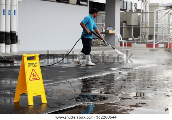 caution wet floor banner and worker cleaning floor with air high pressure machine background
